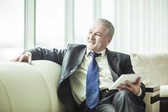 Успешный бизнесмен при цифровая таблетка сидя на софе в личном кабинете Стоковые Изображения