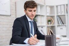 Успешный бизнесмен работая в офисе стоковая фотография