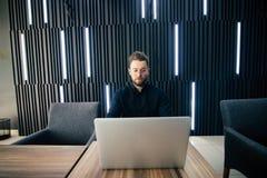Успешный бизнесмен работая на компьтер-книжке в современном роскошном столе офиса Молодой предприниматель удовлетворяемый при рез стоковые фото