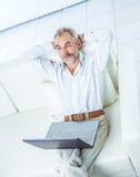 Успешный бизнесмен работая на компьтер-книжке сидя на софе в современном офисе Стоковое Изображение