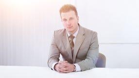 Успешный бизнесмен сидя за столом Стоковое Изображение RF