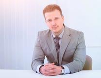 Успешный бизнесмен сидя за столом Стоковые Изображения