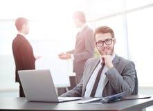 Успешный бизнесмен сидя на таблице с открытой компьтер-книжкой Стоковое Фото