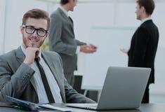 Успешный бизнесмен сидя на таблице с открытой компьтер-книжкой Стоковое Изображение