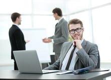Успешный бизнесмен сидя на таблице с открытой компьтер-книжкой Стоковые Фото