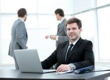 Успешный бизнесмен сидя на таблице с открытой компьтер-книжкой Стоковое Изображение RF