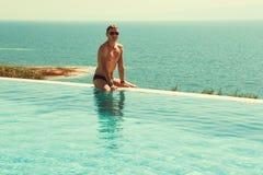 Успешный богатый человек ослабляя в пейзажном бассейне и наслаждается каникулами красивейший массаж головки девушки получая спу к Стоковые Фотографии RF