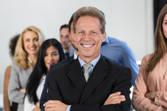 Успешный босс над предпосылкой группы предпринимателей, зрелый руководитель бизнесмена с бизнесменами владением команды уверенно стоковая фотография