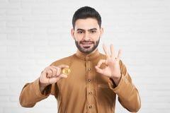 Успешный вклад красивой мужской исламской модели держа золотое bitcoin и показывая одобренный знак Стоковое Изображение