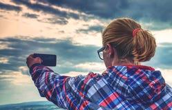 Успешный женский hiker принимает фото на край стоковые изображения rf