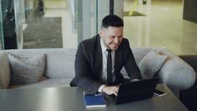 Успешный кавказский бизнесмен в официально одеждах усмехаясь, хлопая и тереть его руки пока получающ хорошие новости видеоматериал
