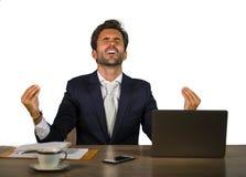 Успешный красивый бизнесмен в костюме работая на столе компьютера офиса празднуя cheerf денег финансового успеха выигрывая усмеха стоковая фотография