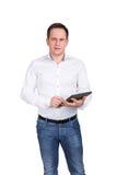 Успешный молодой бизнесмен на белой предпосылке в белой рубашке и голубых джинсах держит прибор таблетки в его руках Стоковая Фотография RF