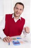 Успешный молодой бухгалтер работая с диаграммами на столе. стоковое фото