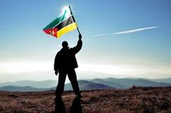 Успешный победитель человека силуэта развевая флаг Мозамбика поверх горы стоковое изображение rf