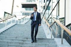 Успешный портрет бизнесмена идя и держа телефон стоковые изображения