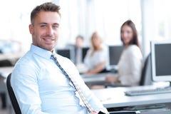 Успешный работник сидя за столом и смотря камеру Стоковые Фото
