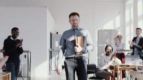 Успешный серьезный молодой кавказский мужской тренер босса входит в современный офис, команду аплодируя ему ЭПОПЕЯ замедленного д акции видеоматериалы