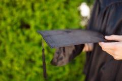 Успешный студент-выпускник, в академичных платьях, держа градацию c Стоковое Фото