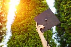 Успешный студент-выпускник, в академичных платьях, поднял вверх градацию c Стоковое Изображение