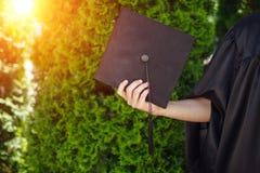 Успешный студент-выпускник, в академичных платьях, поднял вверх градацию c Стоковое Фото