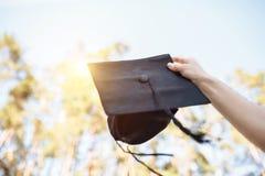 Успешный студент-выпускник, в академичных платьях, поднял вверх градацию c Стоковое Изображение RF