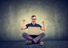 Успешный счастливый человек с кулаками вверх наблюдая компьтер-книжку стоковая фотография