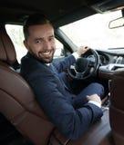 Успешный человек сидя за колесом престижного автомобиля Стоковое фото RF