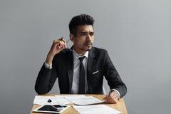 Успешный человек при стекла смотря далеко от камеры, таблетки, телефона и бумаг на таблице Стоковое Изображение RF