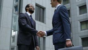 Успешный handshaking около офисного здания, сотрудничество менеджеров, приятельство сток-видео