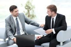 2 успешных бизнесмена обсуждая документы в современном  Стоковая Фотография RF