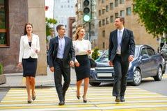 4 успешных бизнесмены пересекая улицу в городе Стоковое Изображение