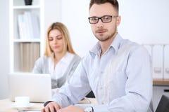 2 успешных делового партнера работая на встрече в офисе женщины tux человека 3 фокуса предпосылки красивейшие Стоковые Фотографии RF