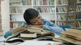 Уставшая африканская девушка студентки лежа на книгах после длиной изучать в библиотеке сток-видео