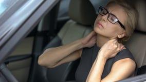 Уставшая дама дела в автомобиле чувствуя сильную боль шеи, воспаление нерва, здоровье стоковое фото