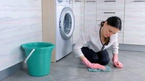 Уставшая женщина в розовом резиновом поле кухни мыть перчаток с тканью и взгляды на камере Серые плитки на поле видеоматериал