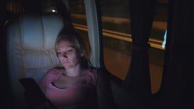 Уставшая женщина едет ночь на автобусе, использует ее телефон видеоматериал