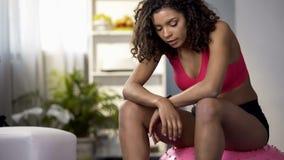 Уставшая женщина отдыхая после разработки, сидящ на шарике фитнеса, тренируя перерыв стоковое изображение