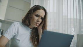 Уставшая женщина смотря ноутбук Портрет грустной женщины используя н видеоматериал