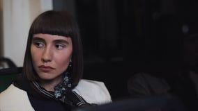 Уставшая и подавленная молодая женщина сидя самостоятельно около окна перехода и думающ о том, что-то Света города видеоматериал