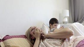Уставшая мать женщины просыпая вверх после спать и ее солнца сидя в кровати и играя мобильные игры на устройстве, смартфоне видеоматериал