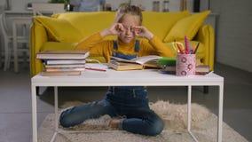 Уставшая школьница тереть ее глаза пока изучающ акции видеоматериалы