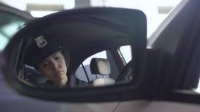 Уставшее patrolwoman принимая стекла, смотря отражение в зеркале заднего вида сток-видео