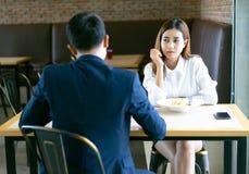 Уставшие пробуренные азиатские усаживание и обед девушки с ее парнем на кафе и смотреть прочь Молодые эмоциональные пары получают стоковое фото