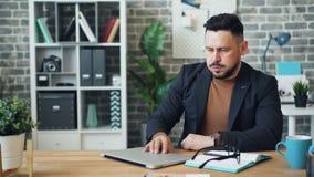 Уставший бизнесмен работая с ноутбуком в отдыхать после этого спать офиса на столе сток-видео
