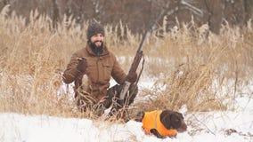 Уставший охотник и его собака имея остатки на холодный зимний день сток-видео