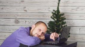 Уставший сонный бизнесмен в офисе на кануне Нового Года Рождественская елка в офисе компьтер-книжка стола владение домашнего ключ акции видеоматериалы