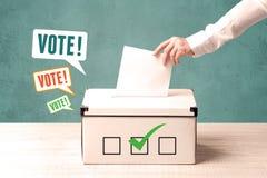 Устанавливать бюллетень голосования в урну для избирательных бюллетеней Стоковые Фотографии RF