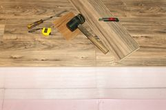 Устанавливать деревянный слоистый настил с изоляцией в дом, пол установки новый после потока Стоковые Изображения
