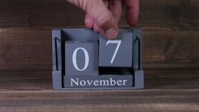 устанавливая дата 07 на деревянном календаре куба на месяцы в ноябре акции видеоматериалы